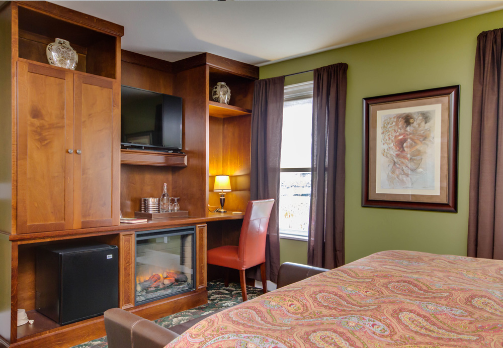 An image of writing desk, mini-fridge, all-season fireplace and TV in Chelsea Room