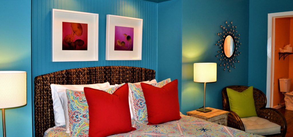 Queen bed and chair in Chicks Beach Room