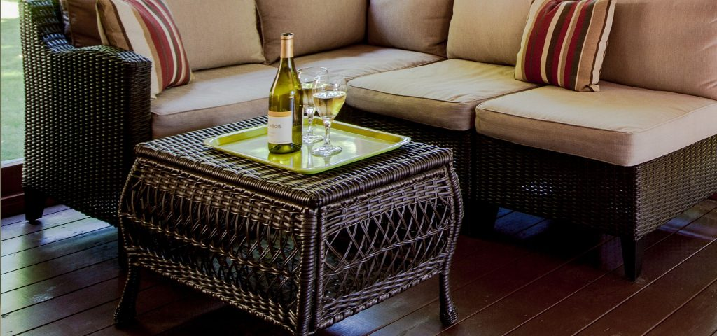 A bottle of wine and two wine glasses on a table on the screened in porch