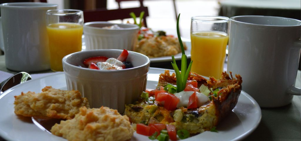Hashbrown quiche with fresh fruit and biscuits